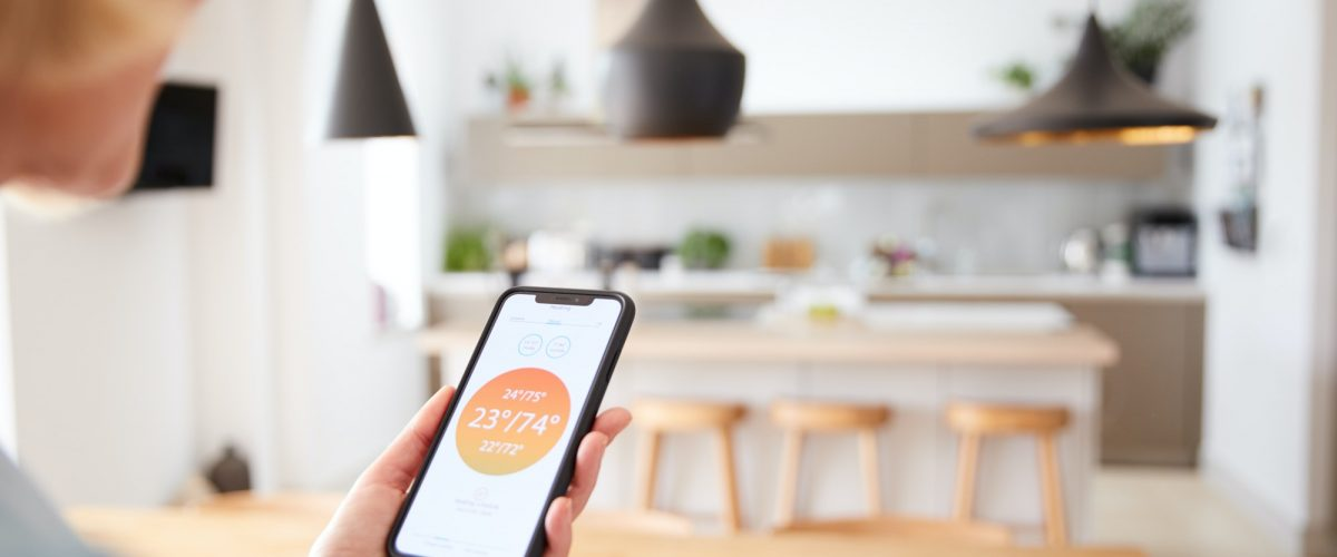Close Up Of Woman Using App On Smart Phone To Control Central Heating Temperature In House